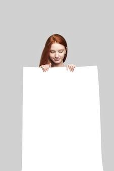 Prise de vue en studio d'une jolie jeune femme rousse tenant un panneau vierge et le regardant en se tenant debout sur fond gris. publicité