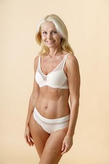Prise de vue en studio d'une magnifique femme mature aux cheveux blonds en sous-vêtements blancs souriant tout en posant pour