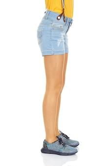 Prise de vue en studio d'un modèle avec de longues jambes et un short en jean