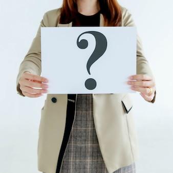 Prise de vue en studio d'officiers féminins incognito non identifiés et méconnaissables en costume d'affaires tenant un panneau en carton avec point d'interrogation montrant la curiosité et un problème douteux sur fond blanc.