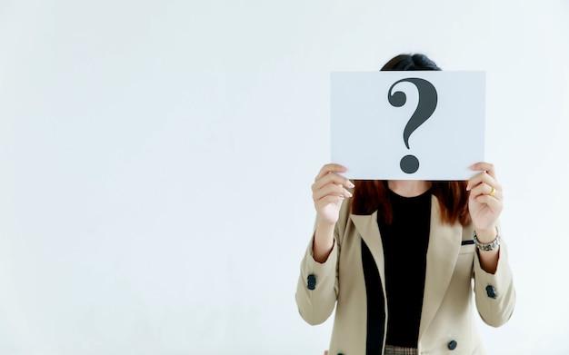 Prise de vue en studio d'officiers féminins incognito non identifiés et méconnaissables en costume d'affaires tenant un point d'interrogation en papier carton signe couverture visage pensant pour des réponses sur fond blanc