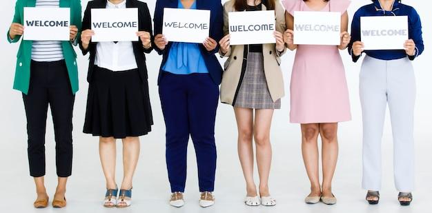 Prise de vue en studio d'officiers féminins sans visage non identifiés et méconnaissables en affaires portant des polices de caractères variées lettres de bienvenue signe papier montrant un accueil chaleureux aux collègues clients sur fond blanc.