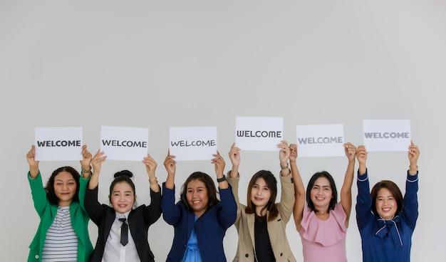 Prise de vue en studio d'un personnel féminin souriant heureux en affaires portant des polices de caractères diverses lettres de bienvenue papier signe au-dessus montrant un accueil chaleureux aux clients clients ou aux nouveaux collègues sur fond blanc.