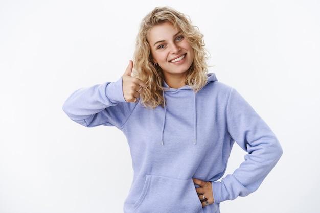 Prise de vue à la taille d'une femme blonde européenne attrayante, agréable et satisfaite, en sweat à capuche, inclinant la tête, montrant joyeusement le pouce vers le haut et l'approbation, recommande un produit cool sur un mur blanc