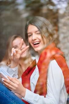 Prise de vue verticale d'une belle jeune femme joyeuse faisant un clin d'œil à la caméra montrant de manière ludique le geste de paix tout en vous relaxant avec un livre au café local, le bonheur des jeunes étudiants insouciants.