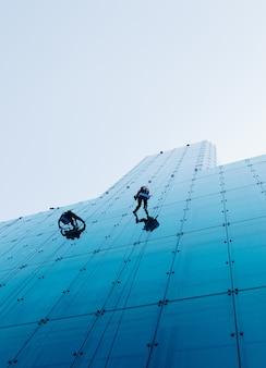 Prise de vue verticale à faible angle de deux personnes escaladant un grand bâtiment de verre pendant la journée
