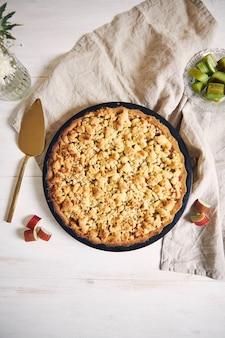 Prise de vue verticale à grand angle d'une assiette de tarte croustillante gâteau rhabarbar et quelques ingrédients sur une table