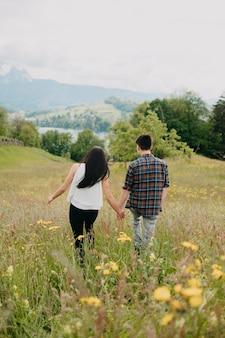 Prise de vue verticale d'un jeune couple aimant marchant sur le terrain
