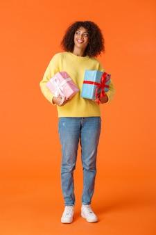 Prise de vue verticale pleine longueur rêveuse et jolie jolie femme afro-américaine regardant autour de lui, tenant des cadeaux, mur orange.