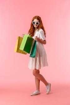 Prise de vue verticale pleine longueur satisfaite, heureuse femme rousse heureuse a terminé ses achats, ravie de combien elle a acheté, regardant dans le sac de la boutique avec un sourire joyeux, debout rose