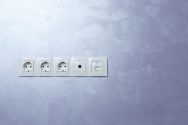 Les prises blanches sur un mur intérieur