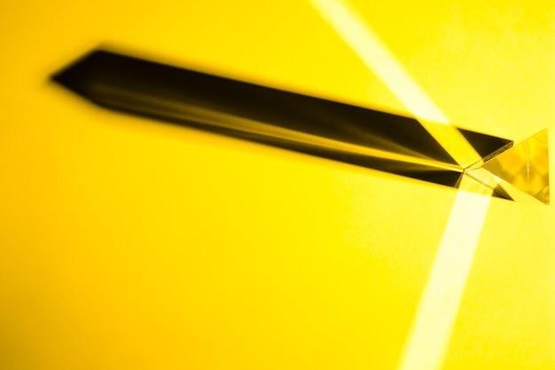Prisme de cristal avec une ombre portée sur un fond jaune