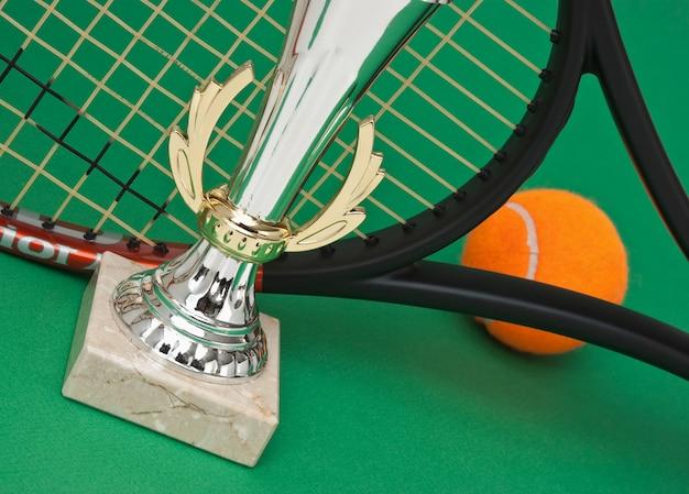 Prix sportifs et raquettes de tennis sur une table verte
