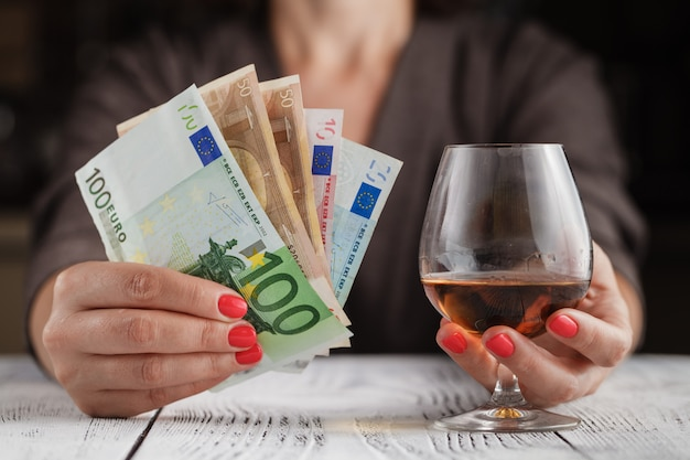 Problème d'alcoolisme. femme prendre un verre de vin sur une table aux tons sombres