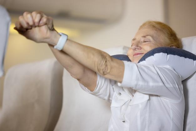 Problème de santé dans un avion, la passagère senior de l'avion a ressenti une douleur à l'épaule après un long trajet en avion