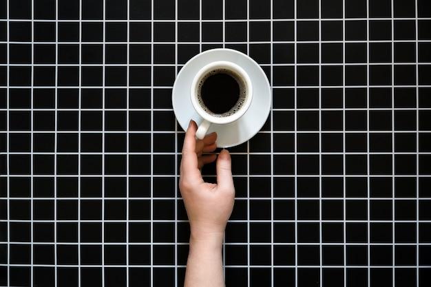 Problèmes de caféine et de sommeil en buvant du café avant de se coucher une tasse de café noir sur un damier noir