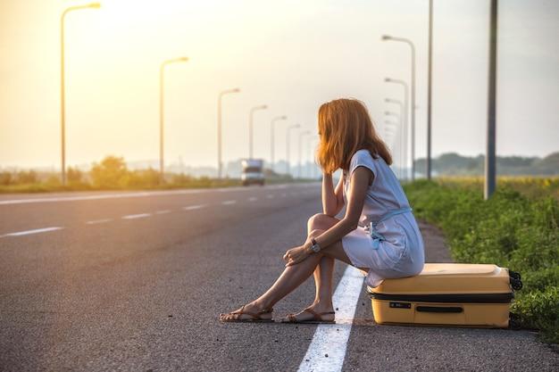 Problèmes dans le voyage. la fille est assise sur une valise jaune au bord de la route