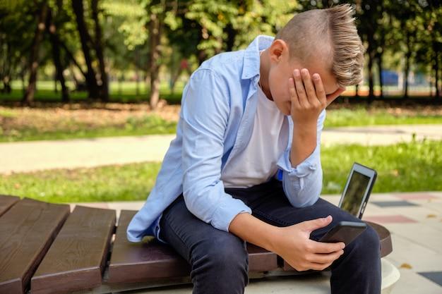 Problèmes des enfants modernes. jeune mec dans le parc avec le téléphone contrarié