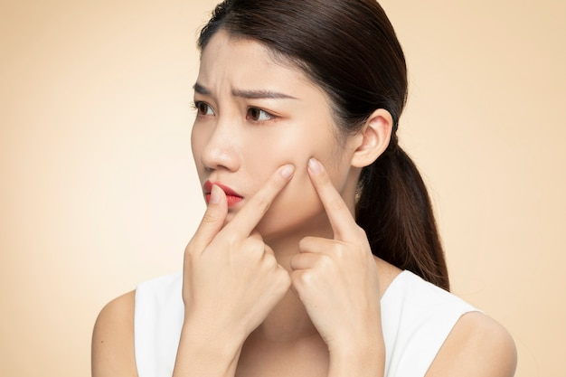 Problèmes de peau du visage des femmes - jeunes femmes malheureuses touchant sa peau sur un fond orange
