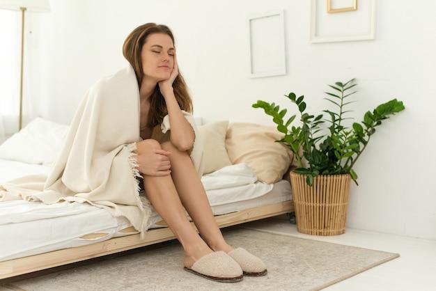Problèmes de sommeil. jeune femme fatiguée dans une couverture avec les yeux fermés dort assise sur le lit.