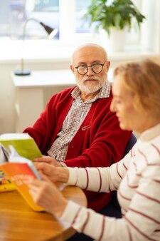 Problèmes de vue. sérieux beau homme âgé portant des lunettes tout en étant assis avec un livre