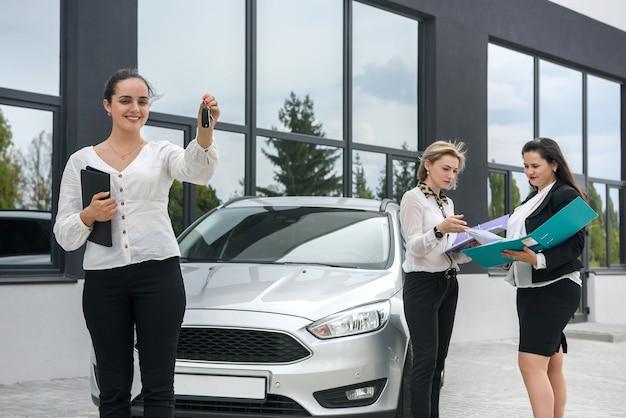 Procédure d'achat de voiture. marchand de femme avec tablette et acheteurs avec dossier debout près de la voiture