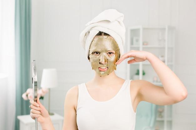 Procédure cosmétique de masque d'or dans le salon de beauté. jolie fille sexy avec une serviette blanche touchant le visage et un masque doré sur le visage, tenant un miroir.