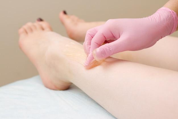 Procédure d'épilation sur jambe belle femme avec du sucre à la crème ou de la cire au miel et des gants roses à la main