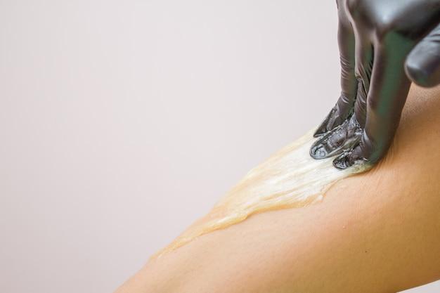 Procédure d'épilation sur jambe belle femme avec de la pâte de sucre ou de cire au miel et des gants noirs à la main