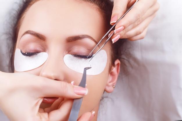 Procédure d'extension des cils. oeil de femme avec de longs cils. cils avec strass. cils, gros plan