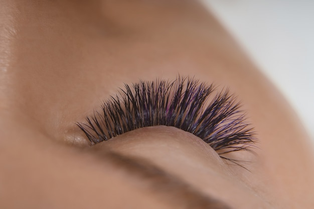 Procédure d'extension des cils. vue rapprochée du bel œil féminin avec de longs cils, une peau saine et lisse.