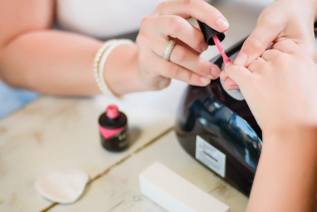 Procédure de manucure avec le vernis à ongles rose