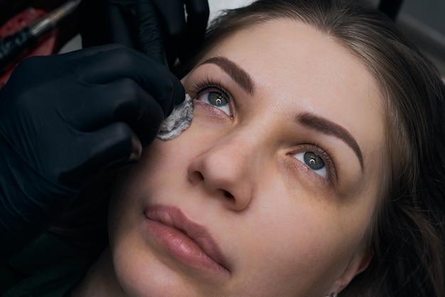 Procédure de maquillage permanent des sourcils. tatouage des sourcils, processus. l'utilisation d'outils par un maître pour le maquillage permanent des sourcils.