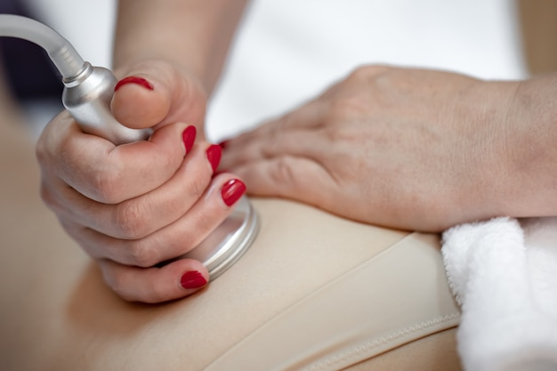 Une procédure de massage anti-cellulite dans un salon de beauté.