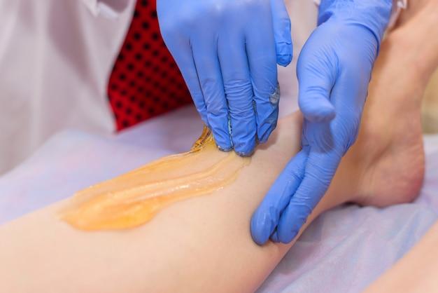 Procédure de mise en forme sur les jambes dans le salon de beauté de la partie du corps