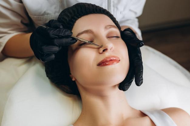 Procédure de nettoyage de la peau avec un outil en acier contre les points noirs et l'acné.