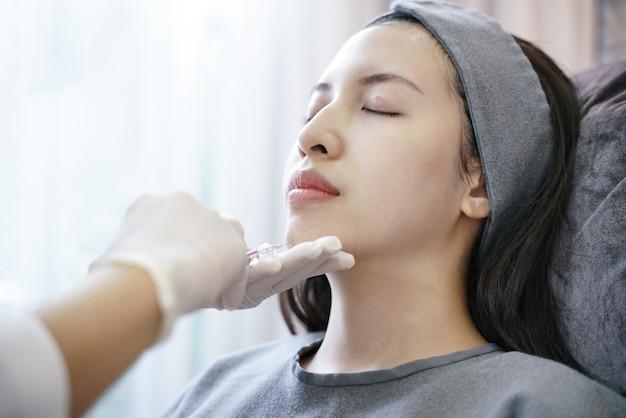 Procédure de rajeunissement lors d'une injection dans une clinique de beauté. femme injection dans son menton.