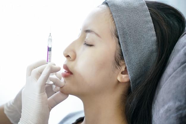 Procédure de rajeunissement lors d'une injection dans une clinique de beauté. femmes injection dans son menton.