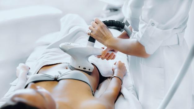 Procédure de soins youskin effectuée avec un appareil à une jeune femme à la femme de spa salonng faisant des procédures de beauté dans un salon moderne.
