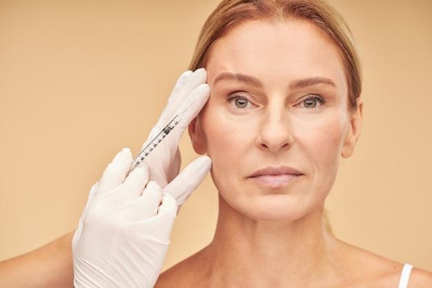 Procédures anti-vieillissement belle femme mature recevant une injection d'acide hyaluronique par une esthéticienne