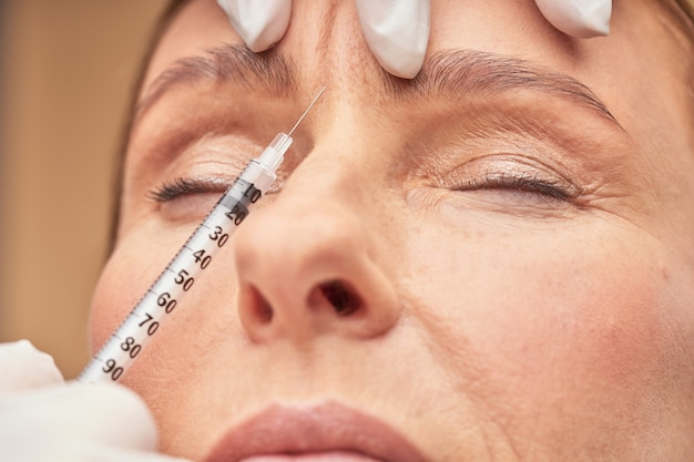 Procédures anti-vieillissement gros plan d'une esthéticienne dans des gants de protection faisant une injection cosmétique dans