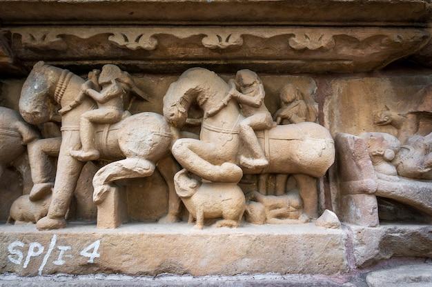 Procession du peuple indien et des chevaux sur le mur de textures en pierre du temple de khajuraho, en inde. site du patrimoine de l'unesco, construit entre 950 et 1150 en inde, appartient à l'hindouisme et au jaïnisme.