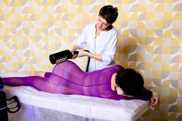 Processus d'appareil de massage de drainage lymphatique. femme en costume blanc se massage anti cellulite