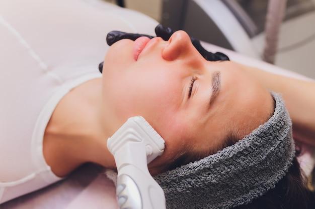 Processus d'appareil de massage de drainage lymphatique lpg. l'esthéticienne thérapeute fait un massage du visage rajeunissant.