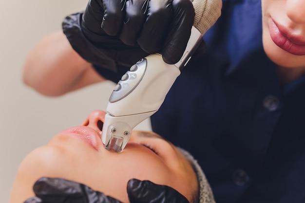 Processus d'appareil de massage de drainage lymphatique lpg. l'esthéticienne thérapeute fait un massage facial rajeunissant pour le modèle.