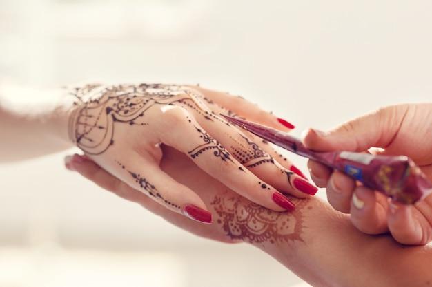Processus d'application du mehndi sur des mains féminines