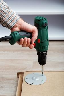 Processus d'assemblage de meubles, le maître collecte les meubles de table à l'aide d'un outil de forage.