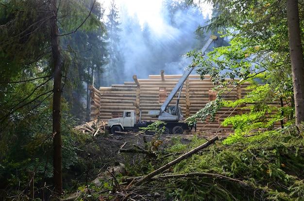 Le processus de construction d'une maison en bois à partir de poutres en bois de forme cylindrique. grue en état de marche