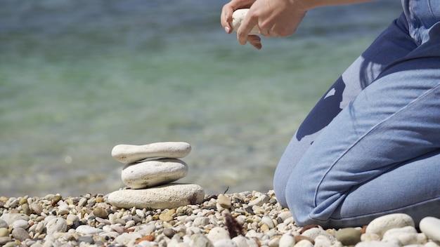 Le processus de construction d'une pyramide de pierres. une main rapprochée place la pierre du sommet au sommet de la pyramide. le concept de calme.