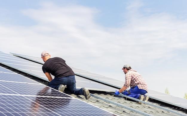 Processus de construction d'une station solaire. les ingénieurs électriciens travaillent à l'installation de panneaux solaires sur une station solaire sur le toit de la maison contre le ciel bleu. concept écologique d'énergie alternative.